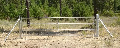 Barbed wire with a large galvanized 4 rail gate