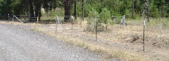 4 strand barbed wire along a dirt road for security and keep out purposes