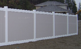 White vinyl frame with pebblestone pickets by valley fence